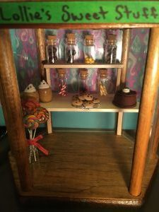 A Fairy's sweet shop with tiny glass jars of various candies, a chocolate cake, cookies, mugs of hot cocoa, and lollipops.