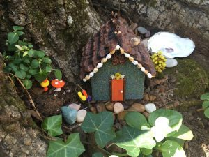 A quaint blue Fairy cottage with pine cone shingles and an orange door.