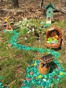 A bejeweled two story fairy house, a tiny fairy wheel, a Fairy Farmer's Market and the Wishing Well nestled among white and purple flowers.