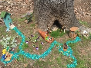 A Fairy village with farmer's market, bake shop, houses, wishing well and a turquoise sidewalk.