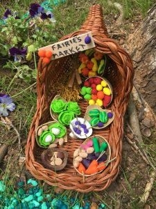 A woven wicker cornucopia filled with tiny clay fruits and veggies.